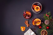 Three glasses with hot mulled wine, Christmas tree branches and an orange on a black background. Flat lay style