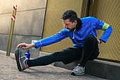 Male doing stretching and listening music after workout. Man resting during city jogging. Runner with mobile phone connected to a smart watch recording data of sport activity with wearable technology