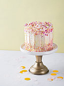 Yellow buttercream ombre birthday cake with colorful sprinkles over yellow background with copy space. Romantic love concept. Valentine's, Mother's Day, Birthday Cake card Background. Close Up.