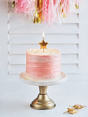 Happy birthday cake shot on a white light background with golden stars candles and space for text. Romantic Celebration Party concept, Valentine's, Mother's Day, Birthday Cake card. Spring time.