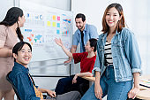 Smart asian startup small entrepreneur  standing confident portrait with  friends partner casual meeting brainstorm with white board and business financce paper chart anslysis in office background