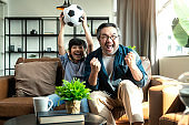 Exited Cheerful Joyful Asian Dad And Son Watching Sports On TV Cheering Favorite Soccer Team, Sitting Together On sofa couch At Home. Weekend With Father. Family time, Online Tv Concept