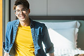 attractive asian mature adult male traveller wear casual cloth and glassses sit smiling relax on bed at hotel travel vacation ideas concecpt