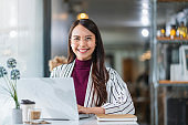 young attractive asian female wear casual cloth hand use smartphone and laptop device comminication social contact in cafe restaruant sit at counter next to big window daylight