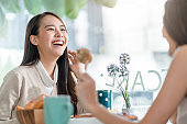 attractive asian female talking good positive conversation to friends with smiling laugh and happiness moment at counter near window at cafe with daylight from garden positive attitude relationship