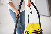 Female hands holding cord from vacuum cleaner