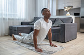 African american guy in white clothes having ahome workout