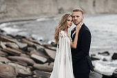 Newlyweds in a wedding dress spend time together outdoors near the ocean on a rocky shore