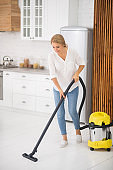 Woman vacuuming white floor in kitchen