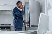 Elegant dark-skinned man standing near the fridge and talking on the phone