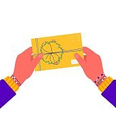 Hands holding envelope with stamps. Woman sending written letter or correspondence through postal service. Hand made gift or present with craft paper letter, ribbon, branches and other decor elements