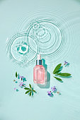 Moisturizing cosmetic products on water with drops. Serum glass bottle and cream jar on aqua surface with waves in sunlight. Concept for advertising organic moisturizing skin care, spa.