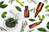 Dropper bottles with oil and mortar with herbs on white table flat lay view. Herbal cosmetics concept