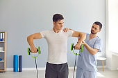 Physiotherapist helping young male athlete recover after sports injury using special resistance band