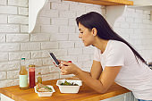 Woman having lunch ordered in meal delivery and using mobile to leave review or to count calories