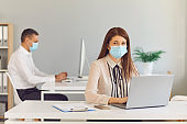Responsible young woman in face mask working in the company office with her colleague