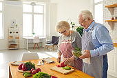 Happy mature couple cooking healthy lunch together in the kitchen of their modern apartment
