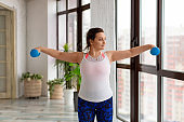 Active lifestyle concept - middle aged woman during home workout with dumbbells