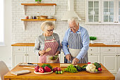 Happy senior couple in aprons cutting vegetables and cooking healthy vegetarian dish together