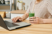 A person holding a drink and using a laptop by table