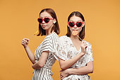 Young stylish female twins in smart dresses and sunglasses having lollipops