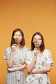 Young gorgeous Asian female twins with lollipops by their eyes looking at you