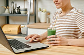 Contemporary female with drink sitting in front of laptop