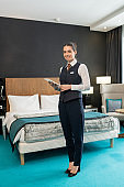 Happy young elegant female worker of hotel standing in front of camera against bed and using tablet