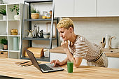 Contemporary businesswoman with laptop bending over kitchen table