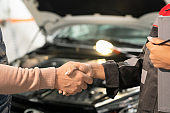 Young professional technician of car service shaking hand of client in workshop