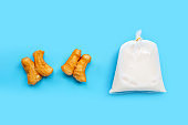 Soymilk in plastic bag with deep-fried dough stick or chinese bread stick on blue background. Top view