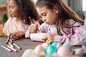 Serious little girl drawing face of Easter rabbit on rolled paper against friend