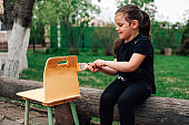 a five-year-old girl paints an old small chair with yellow paint for reuse while sitting on a log in the garden