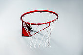 Close up view of red metal basketball hoop with sports net on white wall
