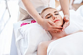 Beautiful young attractive Caucasian woman having body massage by Thai Masseur in spa salon. Beauty treatment and body care lifestyle concept