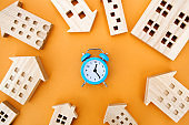 A blue alarm clock and many wooden houses around. Mortgage and loan concept. Real estate and risks. Property insurance. Credit. Tax payment. Utilities. Construction investment. Planning
