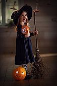 A little girl in a witch costume with pumpkins and a broom. The Halloween holiday