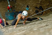 A girl climbs a rock. Woman engaged in extreme sport.