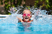 Cute little girl smiling in goggles in the pool on a sunny day. The child splashing water in the pool . Summer vacation