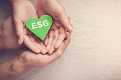 Adult and child hands holding green heart with ESG, Environmental, social and corporate governance concept