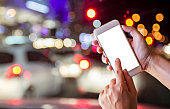 Female hands holding blank screen smartphone at street night in city