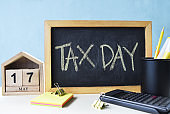 Tax Day concept with wooden calendar 17 May and blackboard