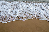Waves hitting sand shore on a late evening. Photo taken in Asia, Thailand