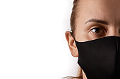 Horizontal close up portrait of a young european woman with brown eyes wearing black face mask, covering her nose, looking straight at camera, isolated over white background, copy space on the left.