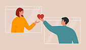 Love online concept. Beautiful young couple celebrating Valentine's day together, having a video call and holding a heart through a screen. Distant romantic relationship.
