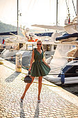 A beautiful woman in a fashionable summer dress and stylish accessories walks in the summer along the promenade next to expensive yachts