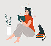 Woman reading a book. Young cute girl sitting on the floor at home with a cat and a pile of books. Studying, learning, self education, love reading concept.
