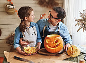Father removing pulp from ripe pumpkin while carving jack o lantern with little daughter for Halloween