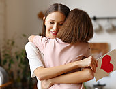 Young mother with greeting card embracing daughter