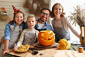 Mother father and children smiling at camera while carving jack o lantern from pumpkin together